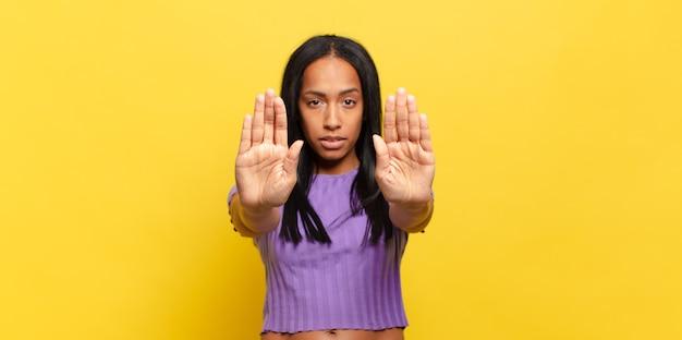 Jovem negra parecendo séria, infeliz, irritada e descontente, proibindo a entrada ou dizendo pare com as palmas das mãos abertas