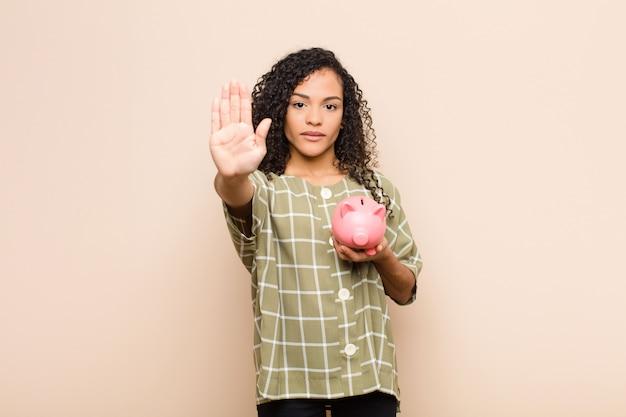 Jovem negra parecendo séria, severa, descontente e irritada, mostrando a palma da mão aberta, fazendo gesto de pare segurando um cofrinho