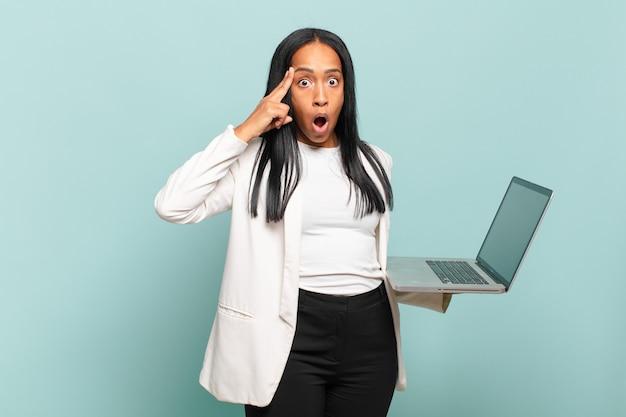 Jovem negra parecendo surpresa, boquiaberta, chocada, percebendo um novo pensamento, ideia ou conceito. conceito de laptop