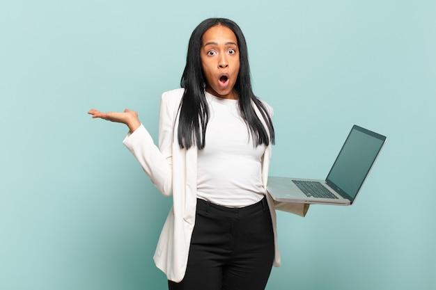 Jovem negra parecendo surpresa e chocada, com o queixo caído segurando um objeto com a mão aberta na lateral. conceito de laptop