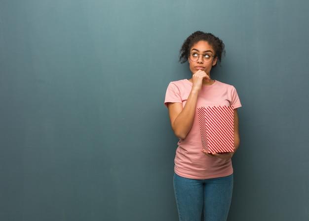Jovem negra, pensando em uma idéia. ela está segurando um balde de pipoca.