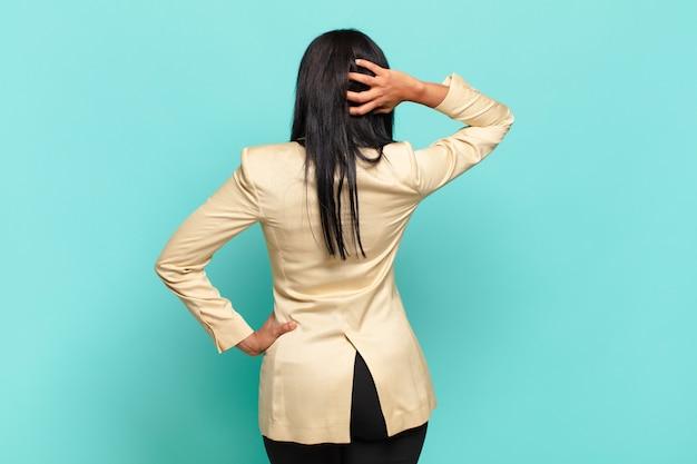 Jovem negra pensando ou duvidando, coçando a cabeça, sentindo-se perplexa e confusa, vista traseira ou traseira. conceito de negócios