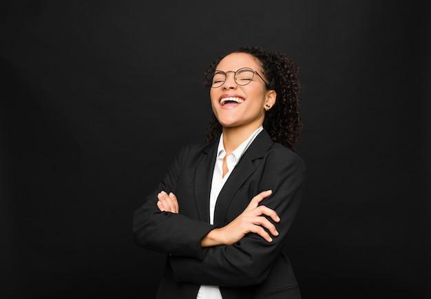 Jovem negra rindo alegremente com os braços cruzados, com uma pose relaxada, positiva e satisfeita contra a parede preta