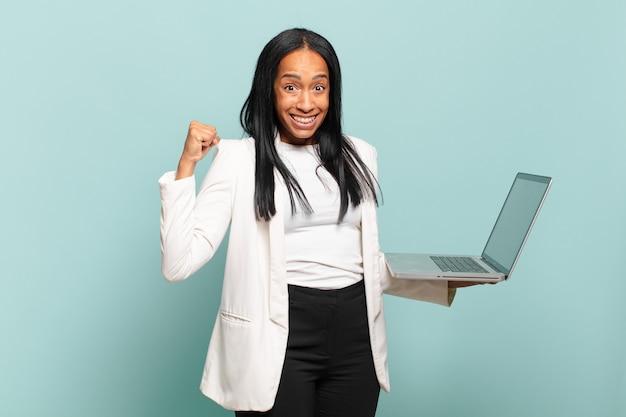 Jovem negra se sentindo chocada, animada e feliz, rindo e comemorando o sucesso, dizendo uau !. conceito de laptop