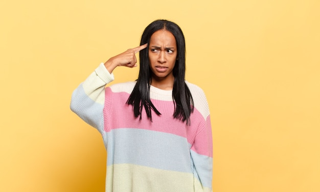 Jovem negra se sentindo confusa e intrigada, mostrando que você é louco, louco ou maluco