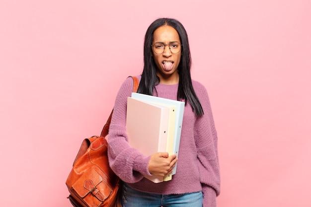 Jovem negra se sentindo enojada e irritada, mostrando a língua, não gostando de algo nojento e nojento. conceito de estudante