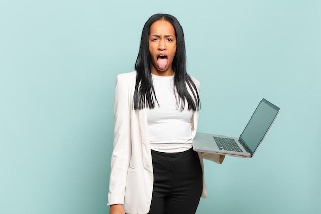 Jovem negra se sentindo enojada e irritada, mostrando a língua, não gostando de algo nojento e nojento. conceito de laptop