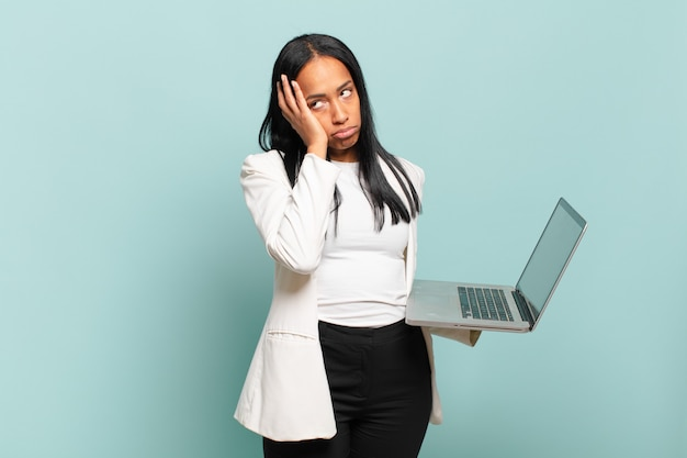 Jovem negra se sentindo entediada, frustrada e com sono depois de uma tarefa cansativa, enfadonha e tediosa, segurando o rosto com a mão. conceito de laptop