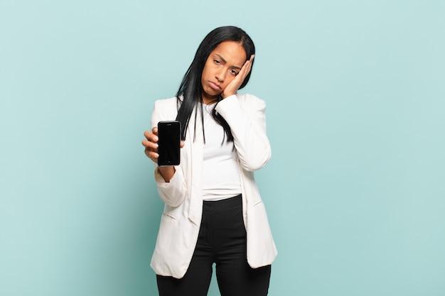 Jovem negra se sentindo entediada, frustrada e com sono depois de uma tarefa cansativa, enfadonha e tediosa, segurando o rosto com a mão. conceito de telefone inteligente