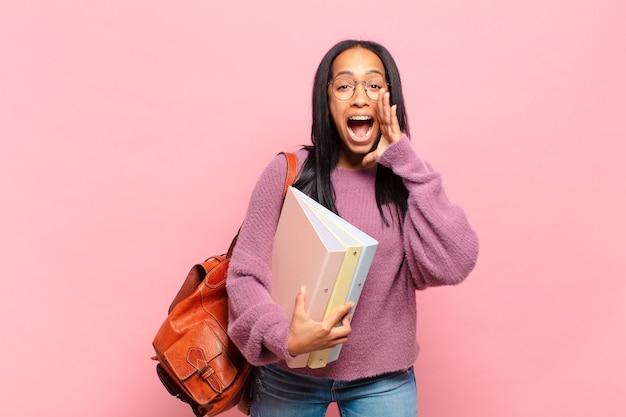 Jovem negra se sentindo feliz, animada e positiva, dando um grande grito com as mãos perto da boca, gritando. conceito de estudante