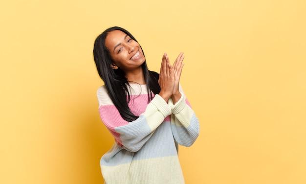 Jovem negra se sentindo feliz e bem-sucedida, sorrindo e batendo palmas, parabenizando-se com aplausos