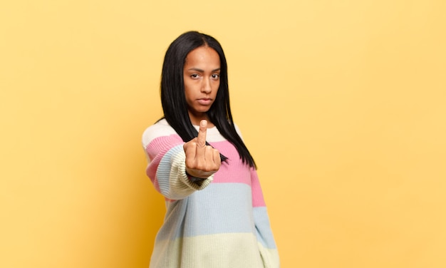 Jovem negra se sentindo irritada, irritada, rebelde e agressiva, sacudindo o dedo do meio, lutando contra