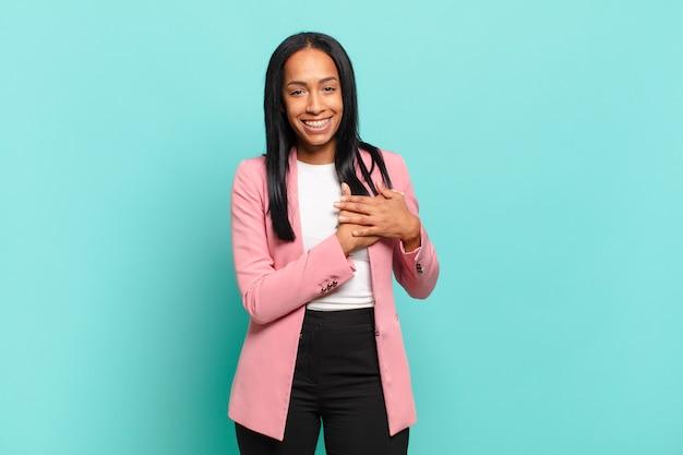 Jovem negra se sentindo romântica, feliz e apaixonada, sorrindo alegremente e segurando as mãos perto do coração. conceito de negócios