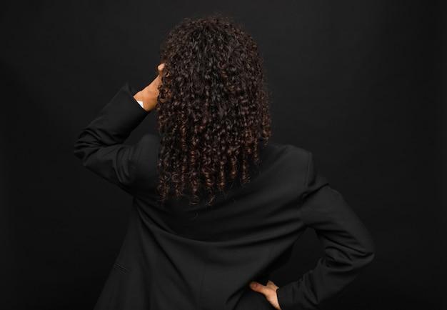 Jovem negra se sentindo sem noção e confusa, pensando uma solução, com a mão na anca e outra na cabeça, vista traseira contra a parede preta
