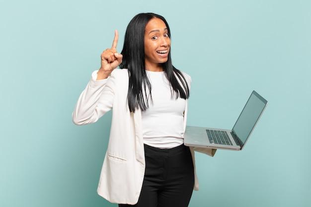 Jovem negra se sentindo um gênio feliz e empolgado depois de realizar uma ideia, levantando o dedo alegremente, eureka !. conceito de laptop