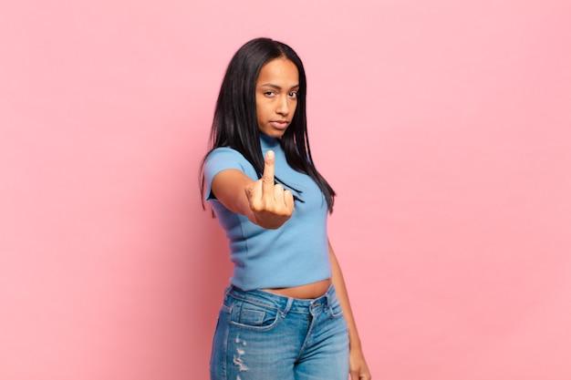Jovem negra se sentindo zangada, irritada, rebelde e agressiva, sacudindo o dedo do meio e revidando