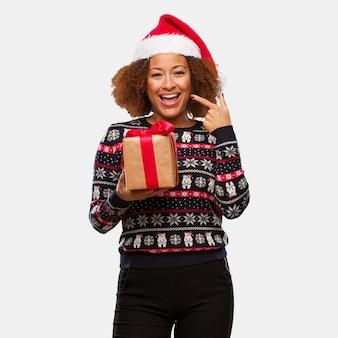 Jovem negra segurando um presente em sorrisos de natal, apontando a boca