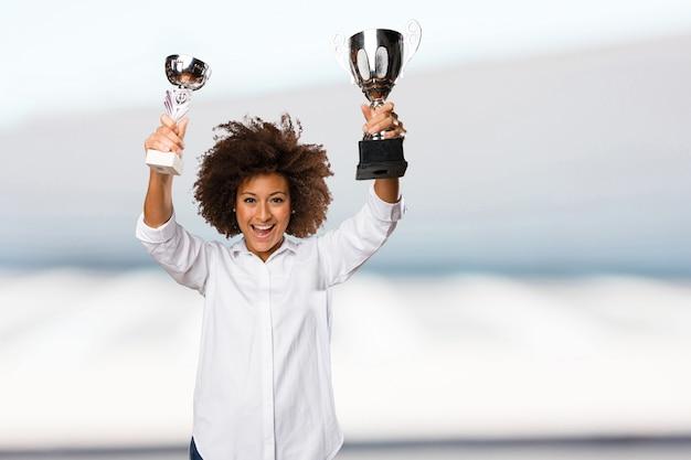 Jovem negra segurando um troféu