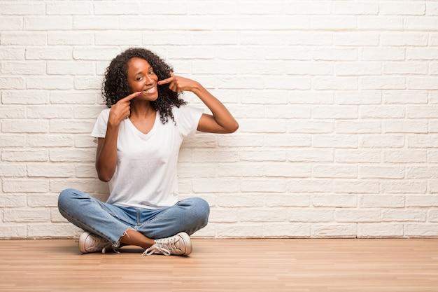 Jovem negra sentada em um chão de madeira sorri, apontando a boca, conceito de dentes perfeitos, dentes brancos, tem uma atitude alegre e jovial