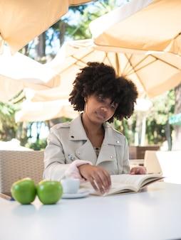 Jovem negra sentada em uma cafeteria, ao ar livre, lendo um livro, algumas maçãs frescas em exposição sobre a mesa