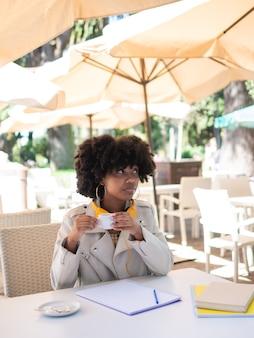 Jovem negra sentada na mesa de um bar tomando um café, ao ar livre