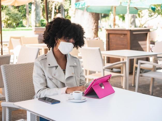 Jovem negra sentada na mesa de um café, do lado de fora, enquanto trabalhava com um tablet e usava uma máscara facial protetora