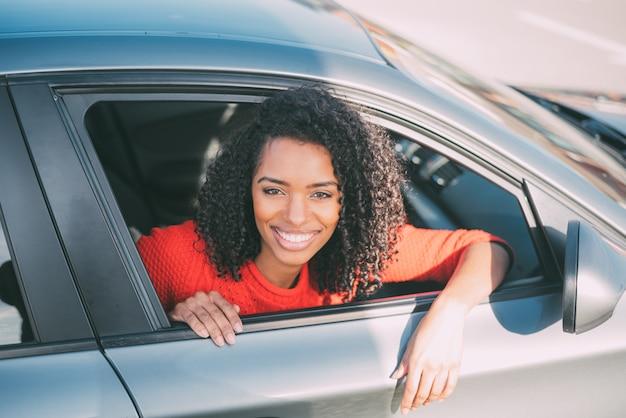 Jovem negra sentada no carro sorrindo