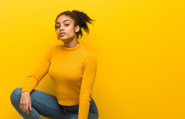 Jovem negra sentada sobre uma parede laranja