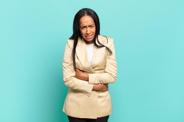 Jovem negra sentindo-se ansiosa, doente, doente e infeliz, com dor de estômago ou gripe. conceito de negócios