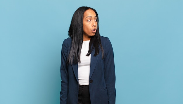 Jovem negra sentindo-se chocada, feliz, espantada e surpresa, olhando para o lado com a boca aberta. conceito de negócios