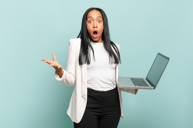 Jovem negra sentindo-se extremamente chocada e surpresa, ansiosa e em pânico, com um olhar estressado e horrorizado. conceito de laptop