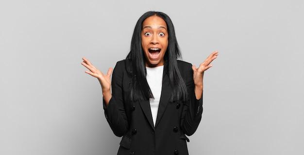 Jovem negra sentindo-se feliz, excitada, surpresa ou chocada, sorrindo e atônita com algo inacreditável. conceito de negócios