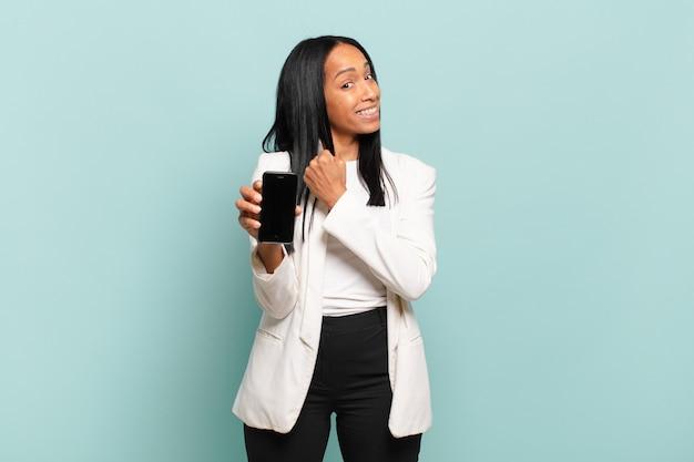 Jovem negra sentindo-se feliz, positiva e bem-sucedida, motivada para enfrentar um desafio ou comemorar bons resultados. conceito de telefone inteligente