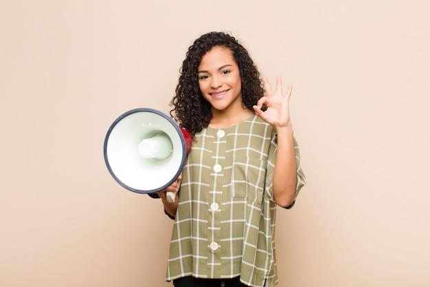 Jovem negra, sentindo-se feliz, relaxado e satisfeito, mostrando aprovação com gesto bem, sorrindo segurando um megafone