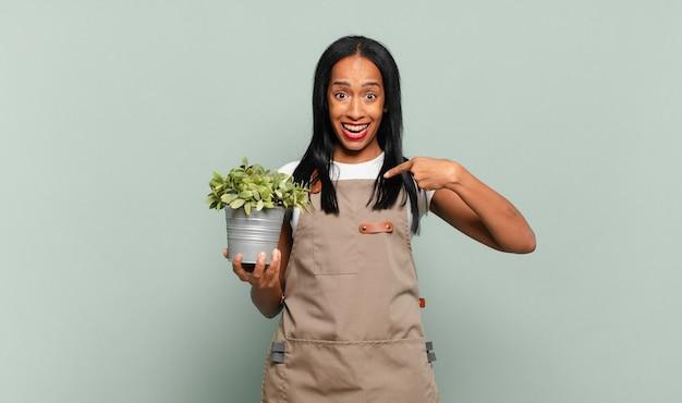 Jovem negra sentindo-se feliz, surpresa e orgulhosa, apontando para si mesma com um olhar empolgado e surpreso. conceito de jardineiro