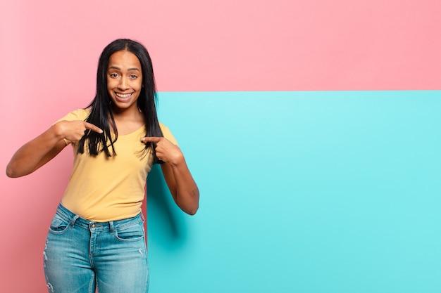 Jovem negra sentindo-se feliz, surpresa e orgulhosa, apontando para si mesma com um olhar empolgado e surpreso. copie o conceito de espaço