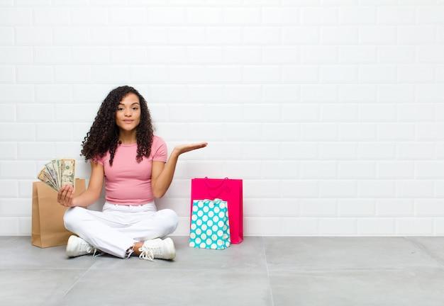 Jovem negra sentindo-se perplexa e confusa, duvidando, ponderando ou escolhendo diferentes opções com expressão engraçada sentada no chão
