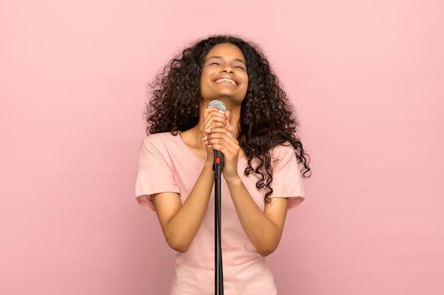Jovem negra sorridente e feliz cantando