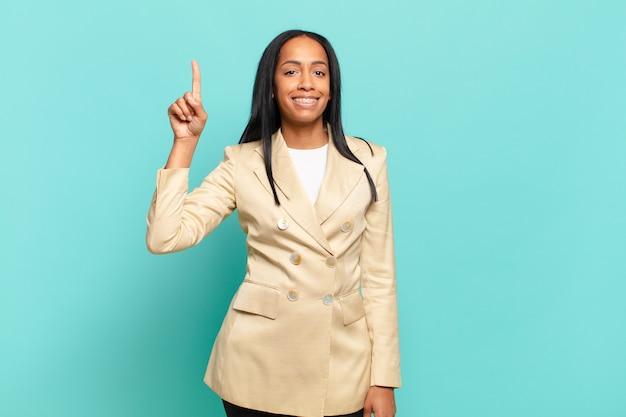 Jovem negra sorrindo alegre e feliz, apontando para cima com uma mão para copiar o espaço. conceito de negócios