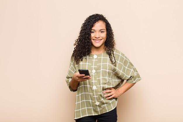 Jovem negra sorrindo alegremente com uma mão no quadril e atitude confiante, positiva, orgulhosa e amigável com um smartphone