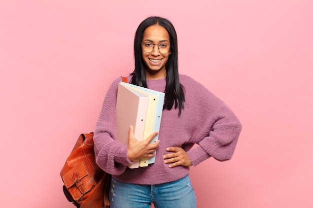Jovem negra sorrindo alegremente com uma mão no quadril e uma atitude confiante, positiva, orgulhosa e amigável. conceito de estudante