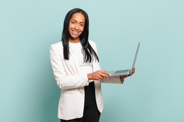 Jovem negra sorrindo alegremente com uma mão no quadril e uma atitude confiante, positiva, orgulhosa e amigável.
