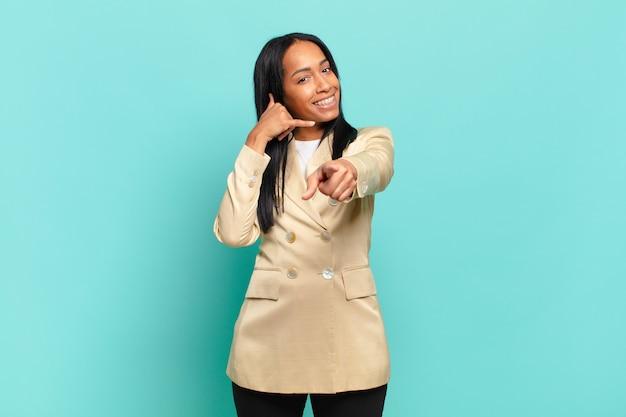 Jovem negra sorrindo alegremente e apontando ao fazer um gesto depois de ligar para você, falando no telefone. conceito de negócios