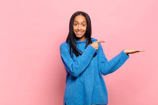 Jovem negra sorrindo alegremente e apontando para copiar o espaço na palma da mão ao lado, mostrando ou anunciando um objeto