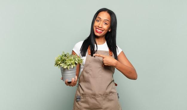 Jovem negra sorrindo alegremente, sentindo-se feliz e apontando para os lados e para cima, mostrando o objeto no espaço da cópia. conceito de jardineiro
