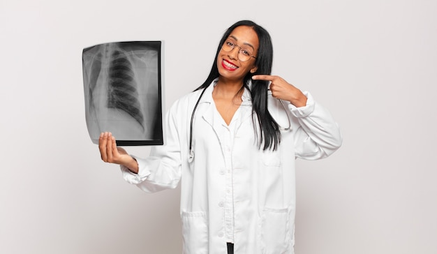 Jovem negra sorrindo com confiança, apontando para o próprio sorriso largo, atitude positiva, relaxada e satisfeita. conceito de médico
