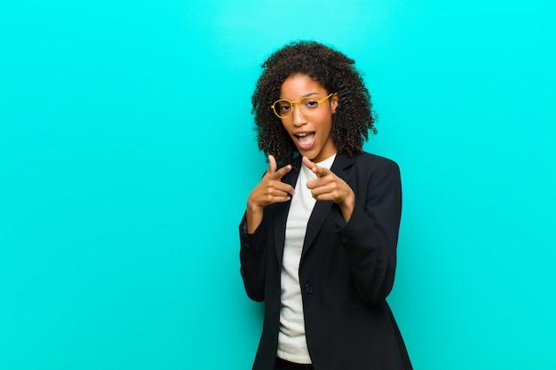 Jovem negra sorrindo com uma atitude positiva, bem-sucedida e feliz, apontando para a câmera, fazendo sinal de arma com as mãos contra a parede azul