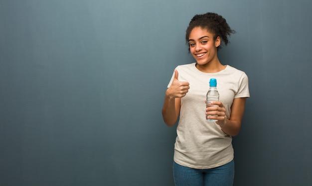 Jovem negra sorrindo e levantando o polegar, ela está segurando uma garrafa de água