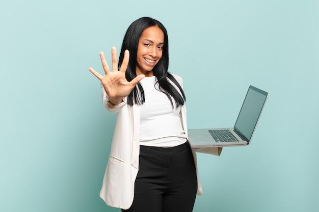 Jovem negra sorrindo e parecendo amigável, mostrando o número cinco ou quinto com a mão para a frente, em contagem regressiva. conceito de laptop