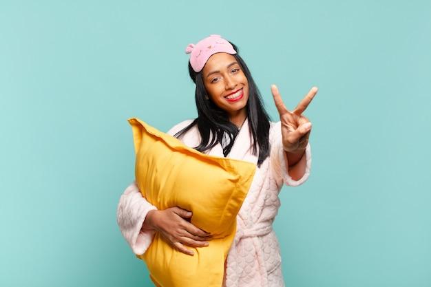 Jovem negra sorrindo e parecendo amigável, mostrando o número dois ou o segundo com a mão para a frente, em contagem regressiva. conceito de pijama